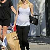 The expectant mother paired a casual white tank with black skinny jeans, white loafers, and oversized round sunglasses during a shopping trip in Beverly Hills.