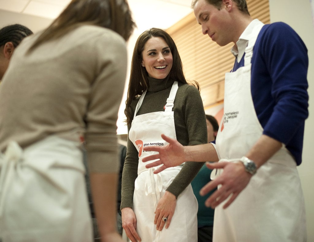 Prince William and Kate Middleton dressed very casually for an event late last year. She chose a sage-green Ralph Lauren turtleneck dress, partially covered by an apron here.