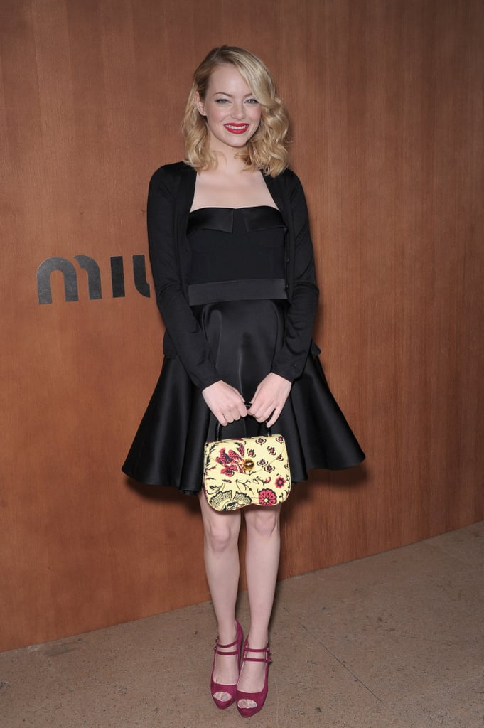 Emma Stone stuck to her signature fit-and-flare silhouette, but in a chic black set, at Miu Miu at Paris Fashion Week. Her bold red lip, printed purse, and magenta double-strap pumps finished off the look.