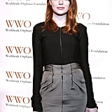 Emma Stone in a grey skirt.
