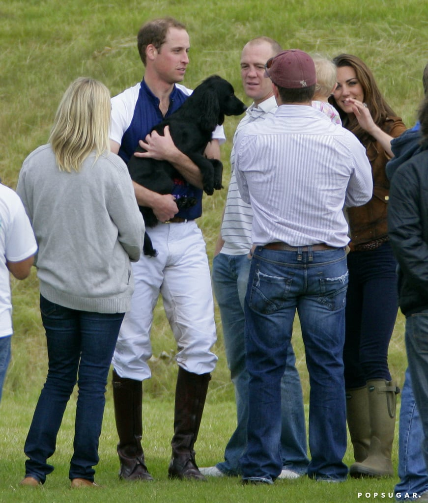 Prince William held onto his pup, Lupo, while Kate Middleton chatted with family members at a polo match in June 2012 in Tetbury, England.
