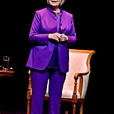 Giving a speech in a head-to-toe purple ensemble.