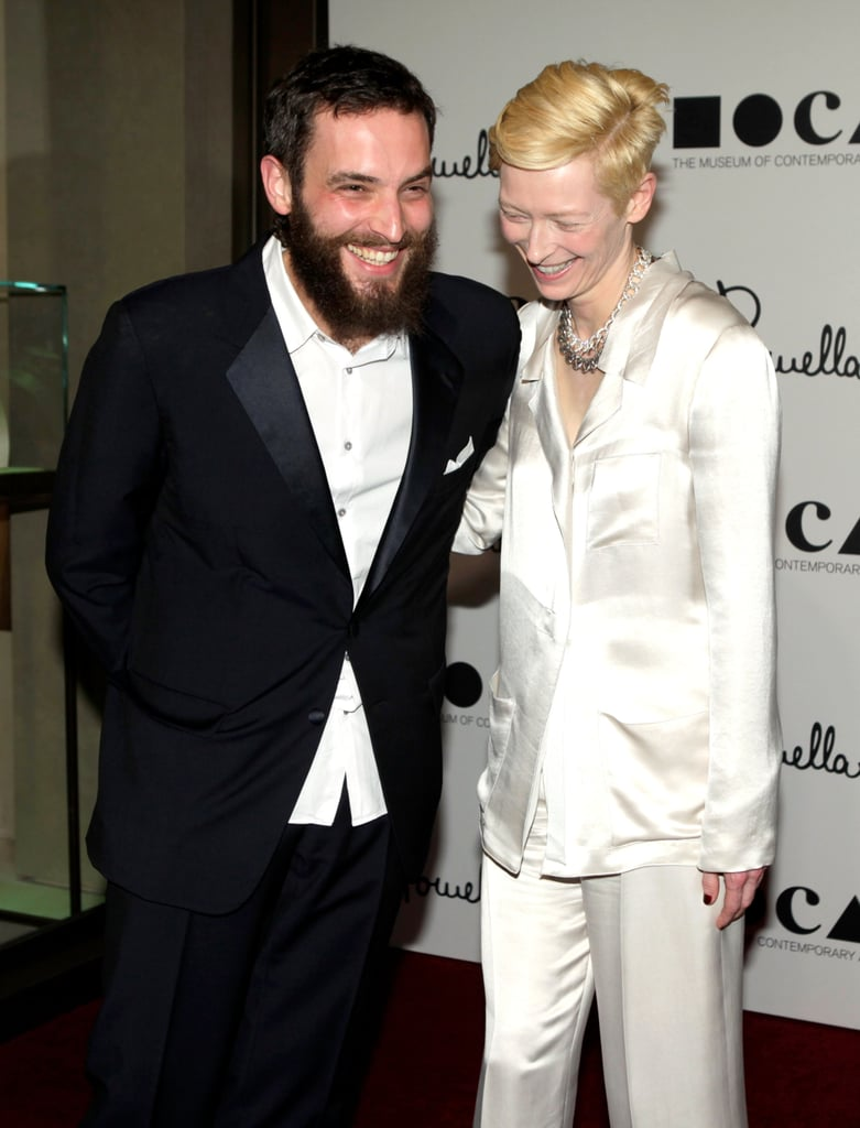 """Tilda Swinton and her partner, Sandro Kopp, know how to work hard and dress hard. The British actress and German visual artist shared the screen in The Chronicles of Narnia (as the White Witch and a centaur, FYI) and travel the world in designer garbs that will have you and your SO feeling short-changed by your wardrobes. Off-screen, they're living in their home in Nairn, Scotland, with Tilda's twins from her marriage to Scottish playwright and artist John Byrne. In fact, albeit an unconventional move, the pair even cohabited with John in the past. Tilda has previously opened up about the arrangement, explaining, """"The father of my children and I are good friends and I'm now in a very happy other relationship. And we're all really good friends. It's a very happy situation,"""" adding, """"Life doesn't have to be complicated"""". We hear you, Tilda! Oh and did we mention that Tilda is basically Sandro's muse? Ro-man-tic.          View this post on Instagram            A post shared by 🔸🔶Sandro Kopp🔶🔸 (@sandrokopp)"""