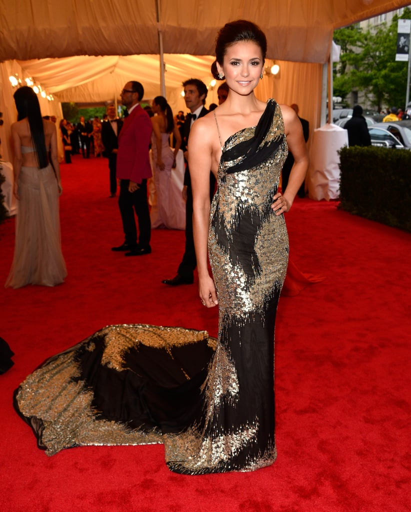 Nina Dobrev stepped out in a Donna Karan Atelier gown at tonight's Met Gala in NYC. The Vampire Diaries star is still glowing from her recent trip to Spain, where she and boyfriend Ian Somerhalder vacationed. This isn't the first time Nina's partnered with Donna Karan on a red-carpet look. Nina was one of the best dressed ladies at the 2011 Primetime Emmy Awards in a strapless, red, figure-hugging gown from the designer — what do you think of her latest look?