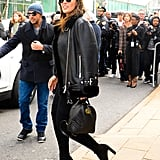 Wearing a leather jacket with black boots, aviators, and a Gucci bag.