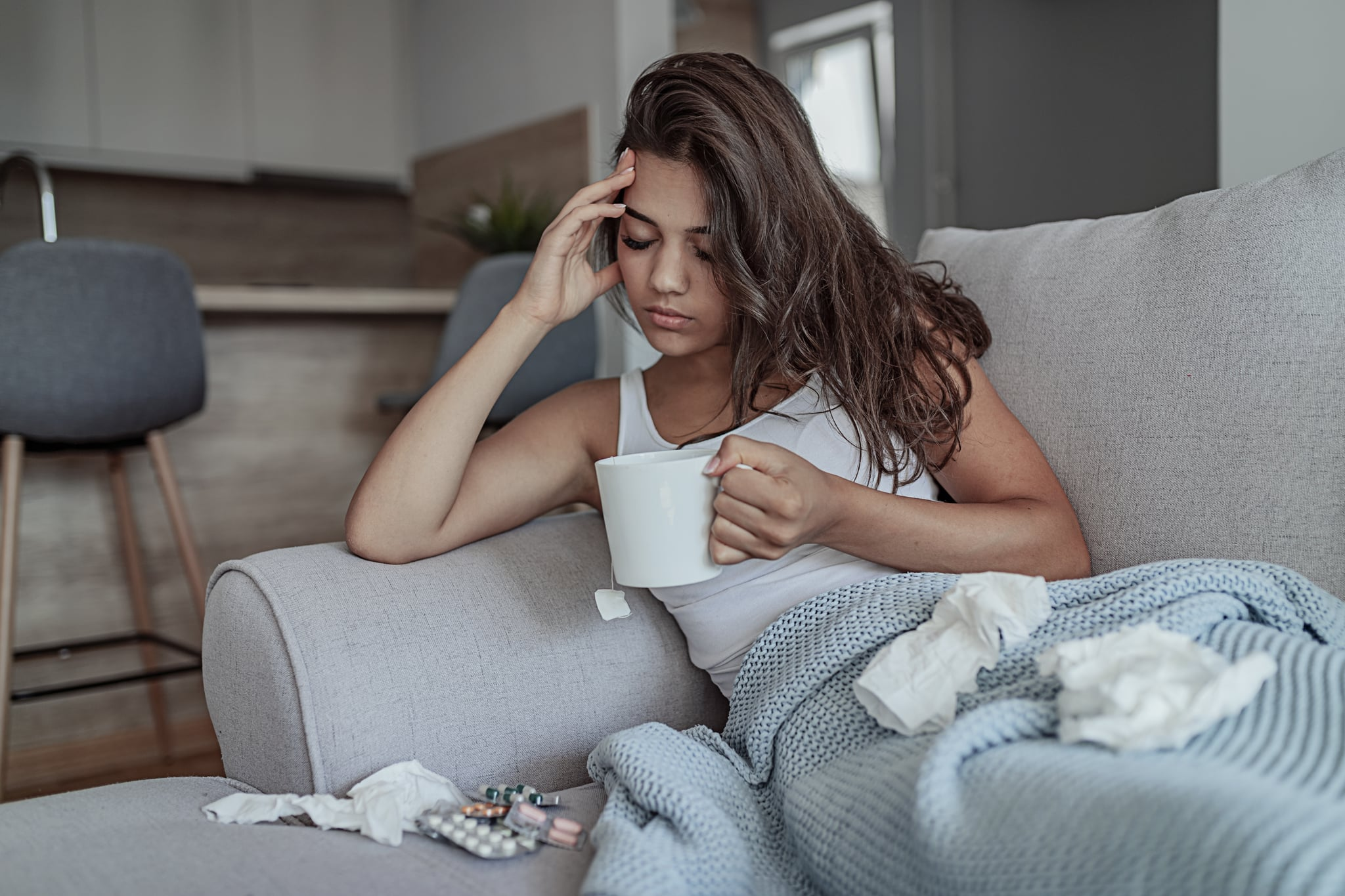 Sick Woman Covered With a Blanket Lying in Bed With High Fever and a Flu, Resting at Living Room. She Is Exhausted and Suffering From Flu While Drinking Tea. Woman With a Strong Morning Headache Sitting on the Bed