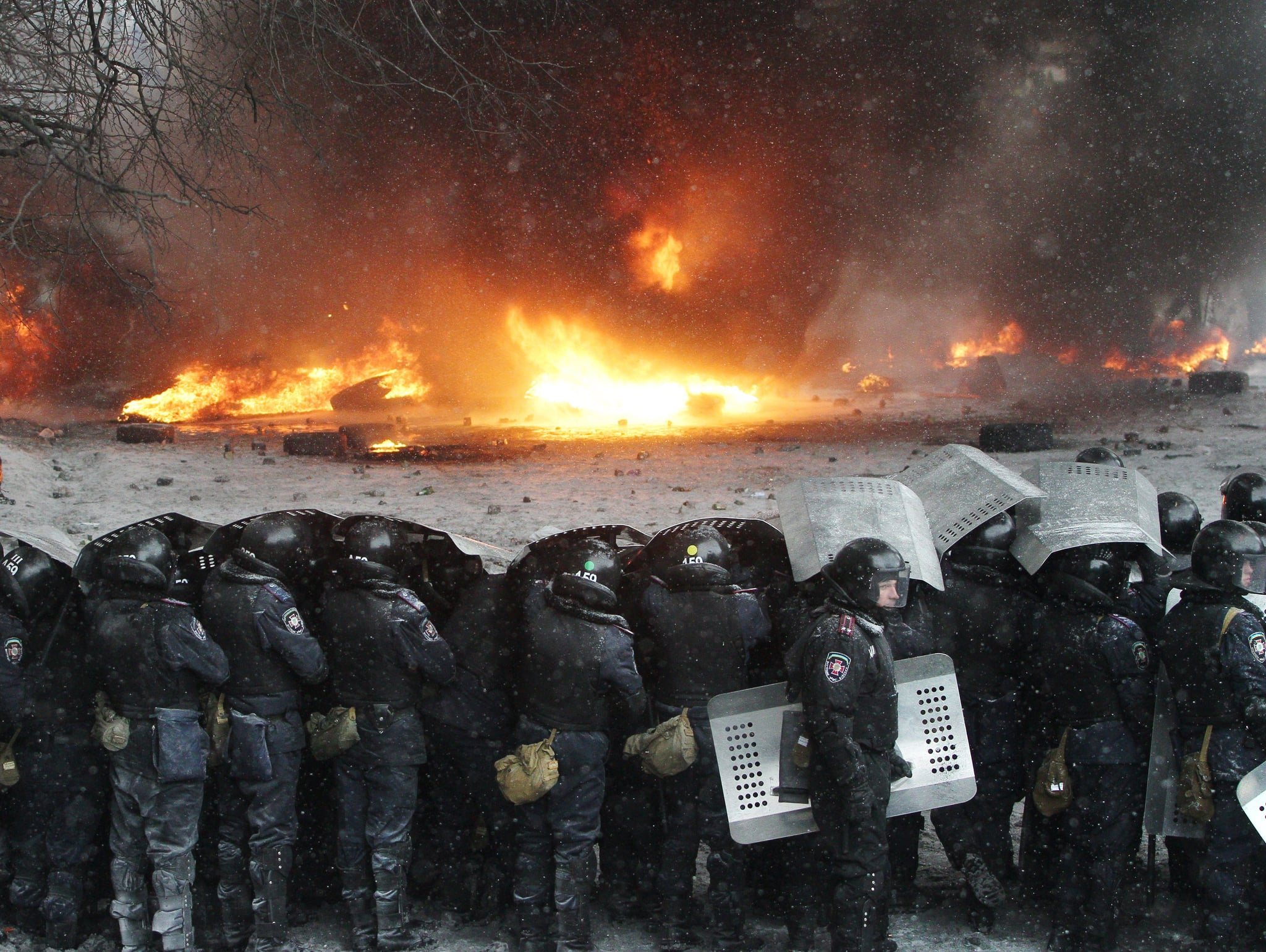 The policemen held up shields to block themselves from falling ashes.