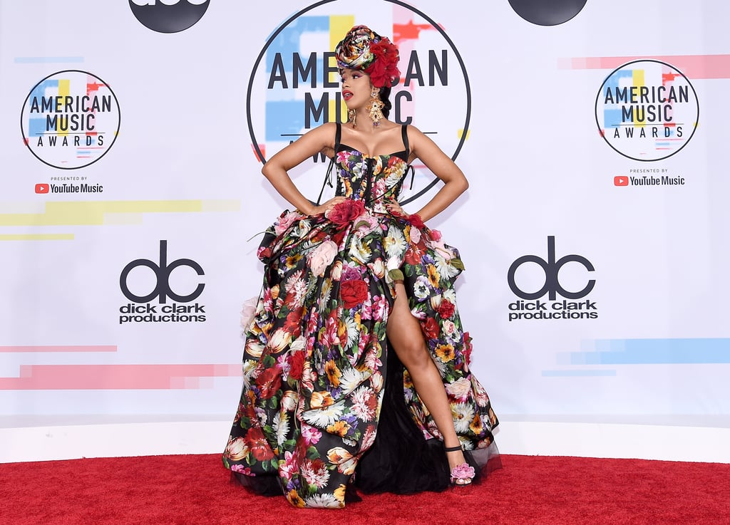 The minute Cardi B stepped foot on the American Music Awards red carpet, you know she was turning heads. The 25-year-old rapper walked side-by-side with husband Offset on Oct. 9, and of course she opted for an outfit that's leagues beyond most award show gowns.  Her floral, corseted dress features a voluminous gathered skirt with a sexy slit through the center. She paired the bold ensemble with a matching headpiece, gold statement earrings, and wraparound floral heels. Your favorite harlequin romance heroine could never. Check out more snaps of her extraordinary outfit ahead, and then see what other stars wore during their night on the red carpet.