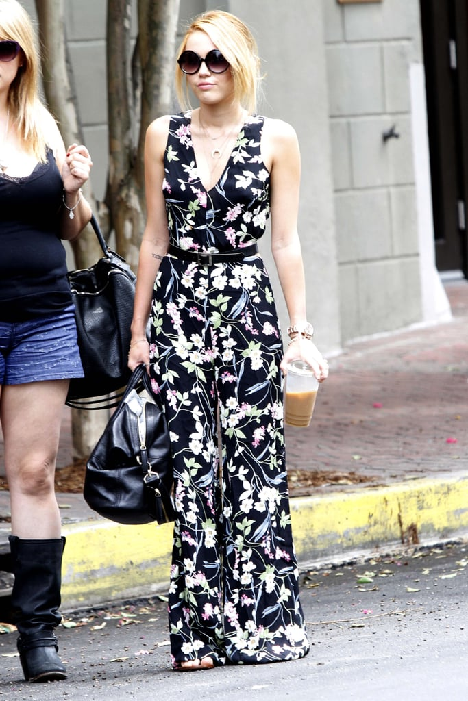 Miley Cyrus rocked a floral jumpsuit to shop in New Orleans yesterday afternoon. She arrived in Louisiana just the day before, having spent the last week at home in LA. Miley went South to meet up with her brand-new fiancé Liam Hemsworth, who's had to break from their private celebrating to get back to work. Liam's shooting Empire State and was photographed multiple times on set last week donning his '70s-era costumes. Miley and Liam got engaged on May 31, and it took about a week before she confirmed the news and started showing off her 3.5 carat diamond. Miley Cyrus's engagement ring was on display at a Malibu photo shoot, and she donned the Neil Lane design while out browsing NOLA's stores as well.