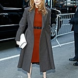 Jessica Chastain headed to the Calvin Klein Collection show in an orange-red sheath dress, purple patent pumps, a gray coat, and a white clutch.