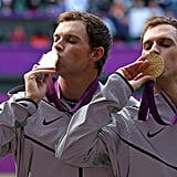 Twin brothers Mike and Bob Bryan kiss their gold medals after winning the men's tennis doubles final against France.