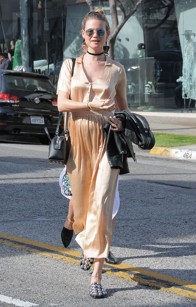 """Behati Prinsloo's baby bump is getting bigger by the second! On Tuesday afternoon, the Namibian beauty, who is pregnant with her first child with husband Adam Levine, was spotted doing some baby shopping at LA's Bel Bambini with pal Lily Aldridge. The model, who looked carefree and relaxed in a flowy gold dress, gave cameras yet another glimpse at her blossoming belly while making her way back to her car. Over the weekend, Adam took to Instagram to gush over his wife and shared a snap of her precious bare belly, writing, """"My two favorite laker fans."""" Keep reading for more pictures, and then get a peek at Behati's belly from all angles."""