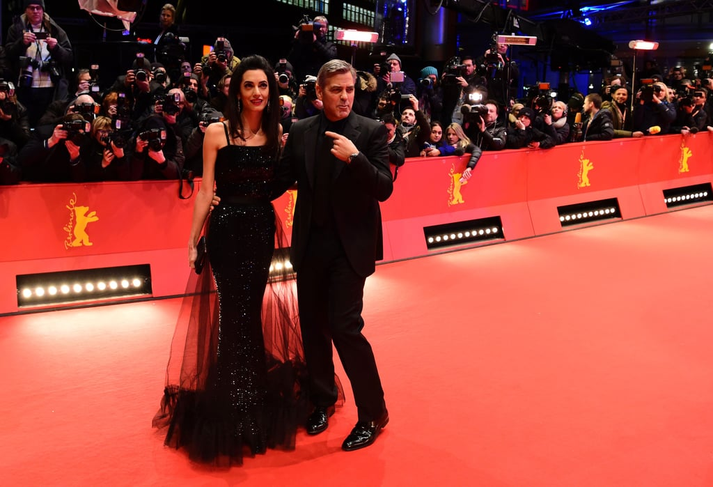 George Clooney is in Germany to promote his latest film, Hail, Caesar!, and after spending the day palling around with costar Channing Tatum, the actor hit the red carpet with his gorgeous wife, Amal, for the movie's premiere at the Berlinale Film Festival on Thursday. Amal stunned in a black layered gown for the event and stayed close to George as they posed for sweet photos. Inside, the couple held hands in their seats and were all smiles for the camera. Just last week, Amal accompanied George to the comedy's LA premiere, and the two basically looked like a Nicholas Sparks movie poster come to life. While in Los Angeles, George made an appearance on The Ellen DeGeneres Show and revealed that it actually took Amal nearly half an hour to accept his marriage proposal back in April 2014. Keep reading to see George and Amal on the red carpet in Berlin, then check out even more of their most romantic photos.