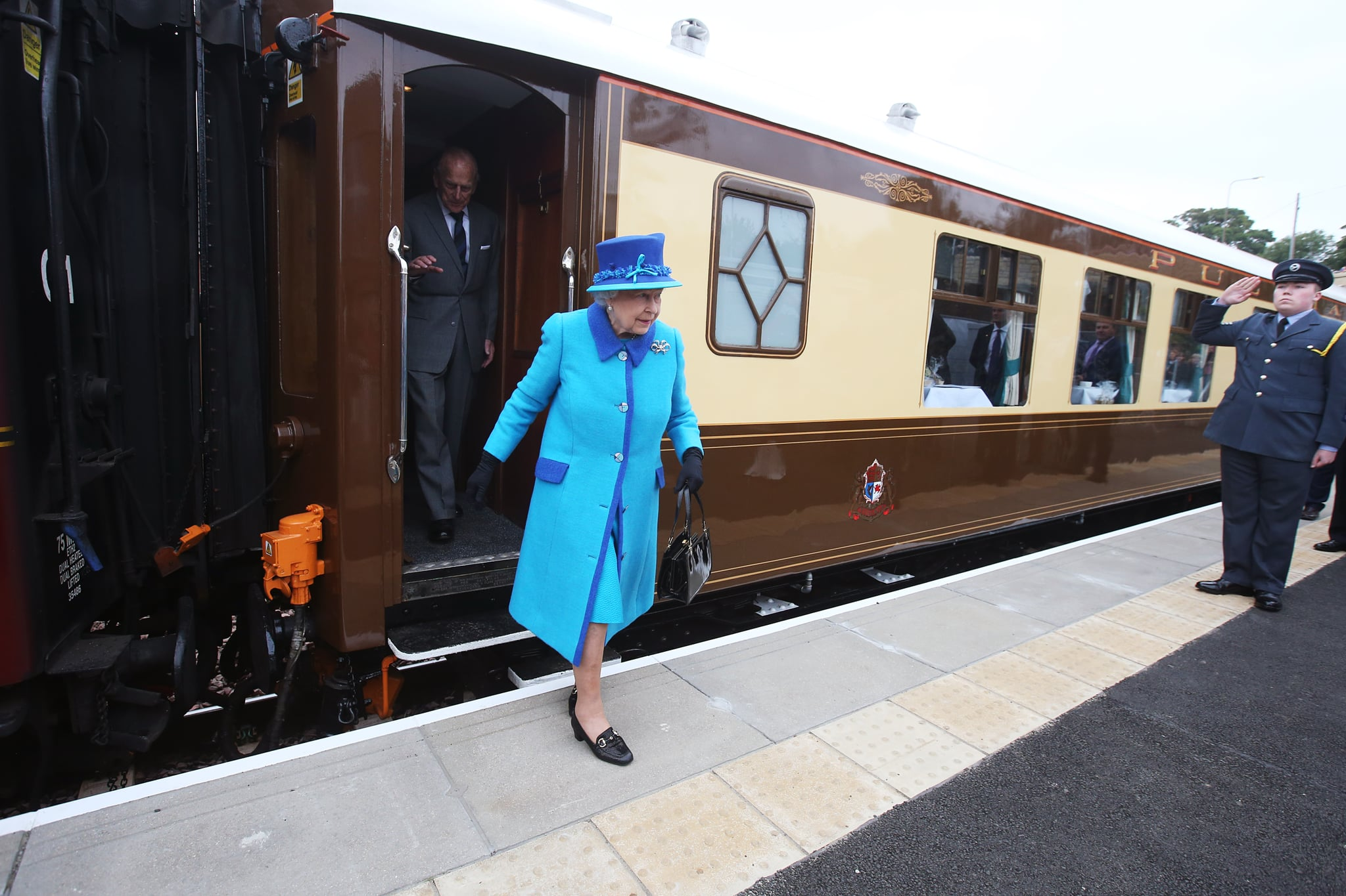 NEWTONGRANGE, SCOTLAND - SEPTEMBER 09:  Queen Elizabeth II arrives to greet well-wishers before she unveils a commemorative plaque at Newtongrange railway station on board the steam locomotive 'Union of South Africa' on the day she becomes Britain's longest reigning monarch on September 09, 2015 in Newtongrange, Scotland. Today, Her Majesty Queen Elizabeth II becomes the longest reigning monarch in British history overtaking her great-great grandmother Queen Victoria's record by one day. The Queen has reigned for a total of 63 years and 217 days. Accompanied by her husband and Scotland's First Minister Nicola Sturgeon she will officially open the new Scottish Border's Railway which runs from the capital to Tweedbank.  (Photo by Andrew Milligan - WPA Pool/Getty Images)