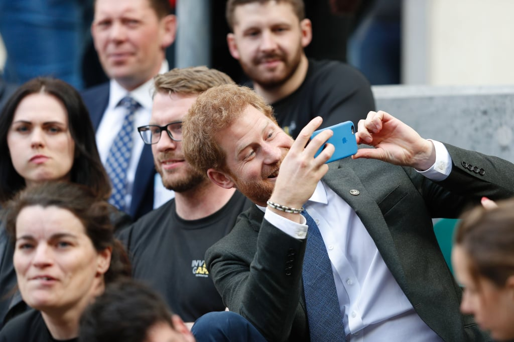 Have you ever noticed that whenever Prince Harry is doing something involved with the Invictus Games, he looks like he's having the time of his life? A few weeks after hanging out with an adorable 2-year-old at the UK team trials for the athletic competition, he brought athletes who participated in the 2014 and 2016 Invictus Games to watch the annual Army Navy rugby match in London on Saturday. Harry, who will be attending Pippa Middleton's wedding with girlfriend Meghan Markle later this month, was happy to goof off with everyone in the stands, taking selfies and making funny faces. As Patron of the athletic competition — which is the only international sport competition for wounded, injured, and sick servicemen and women — he's been extremely involved since its inception. Last year, he kicked off the Invictus Games in Orlando, FL, with the help of Michelle Obama, and has kept in touch with the athletes ever since. Harry's Invictus Games Foundation was the official charity of this year's rugby match, so he also went onto the field to chat with some of the players from the Royal Navy and British Army, and to help sing the national anthem.