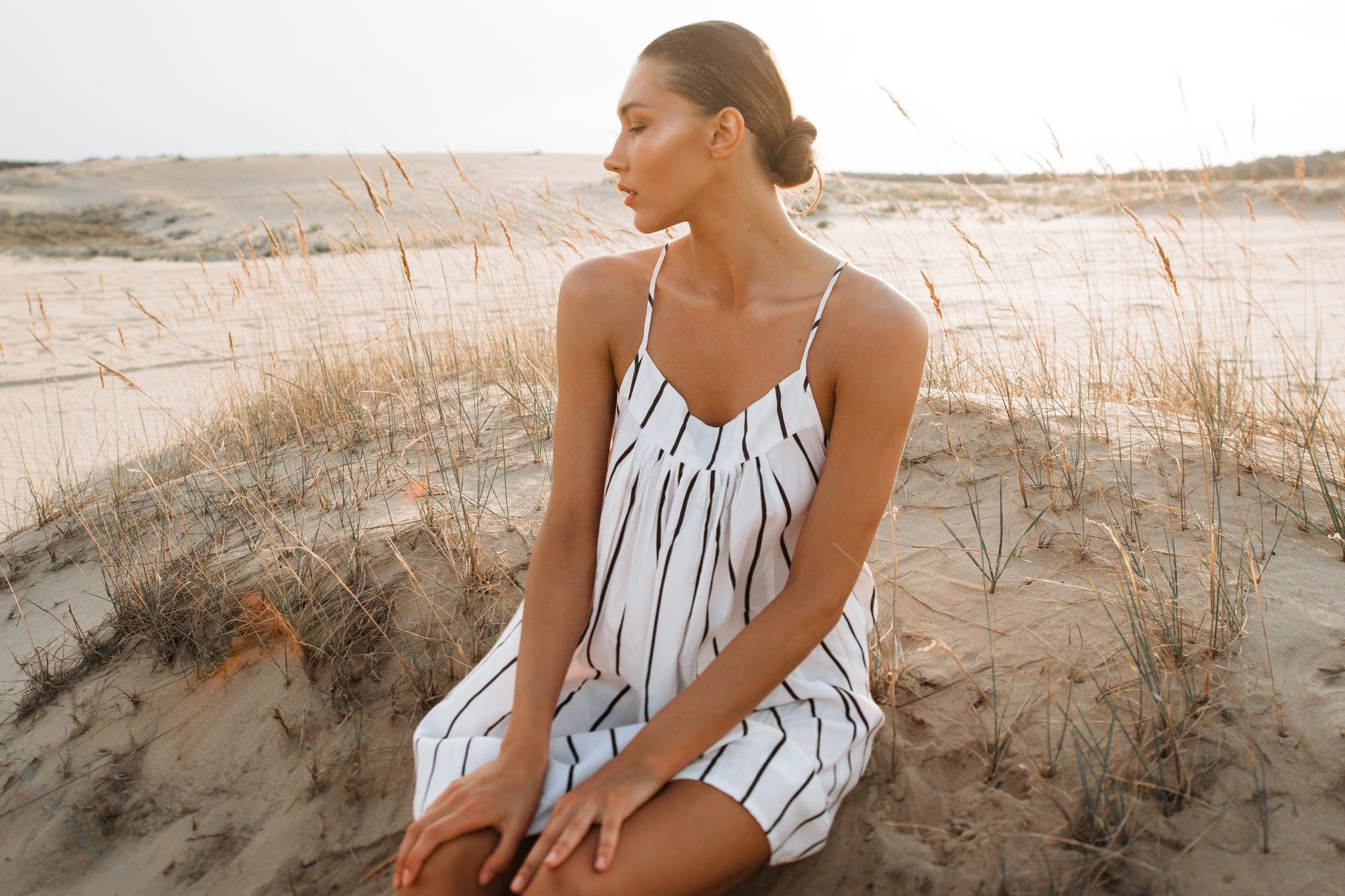 Girl in a striped dress in the evening desert. Model fashion in white dress on sand.; Shutterstock ID 1245789838; Job: -