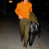 Gigi Styled Her Gucci Loafers With Satin Green Pants, an Orange Hoodie, and Matching Sunglasses