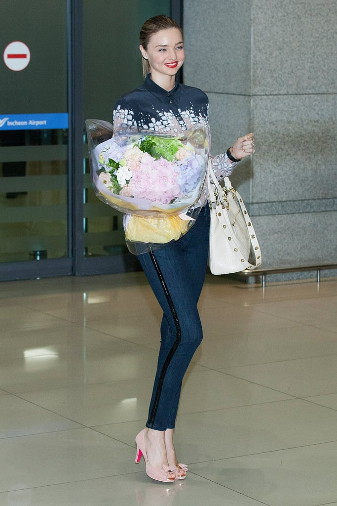 Miranda Kerr was showered with flowers when she landed in Incheon, South Korea, yesterday. She showed off her long legs in skinny jeans and nude pumps as she made her way through the airport. Miranda is in Korea to make appearances on two TV shows, SNL Korea and Gag Concert, as well as throw the first pitch at the Doosan Bears vs. SK Wyverns game this week. She will also reportedly be making an appearance at a makeup show at the Shinsegae department store, which is fitting as she recently spoke to us about her beauty essentials — check out Miranda's beauty secrets! Miranda isn't the only celebrity who recently landed in the Asian country, as Brad Pitt was in South Korea yesterday as well to continue his press tour for World War Z.