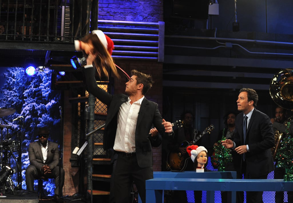 Zac Efron suited up for an appearance on Late Night With Jimmy Fallon in NYC last night. Zac was there to talk about New Year's Eve, which hits theaters tomorrow, but the interview took a fun turn when Jimmy asked Zac to play a festive basketball game. Zac and Jimmy went head-to-head in a shoot out, though instead of basketballs they used holiday items like mini Christmas trees. Jimmy ended up winning the match, but Zac was a good sport about the loss. Zac threw on a tie later in the evening to attend the premiere of New Year's Eve with Jessica Biel, Michelle Pfeiffer, and Sarah Jessica Parker. Zac and Michelle also shared the red carpet at Monday's LA screening, but their costars Ashton Kutcher and Lea Michelle managed to steal much of the attention with their flirtatious behavior. Zac's the one taking the spotlight in our favorite shirtless star of 2011 poll, though, since he's got the most votes behind Robert Pattinson.