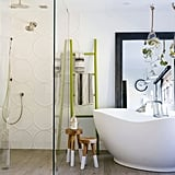 The master bath is an enviable oasis created with designer Kim Lewis. A freestanding tub, open double shower, hanging terrariums, and Ann Sacks tile blend luxury spa amenities with a farmhouse sensibility.