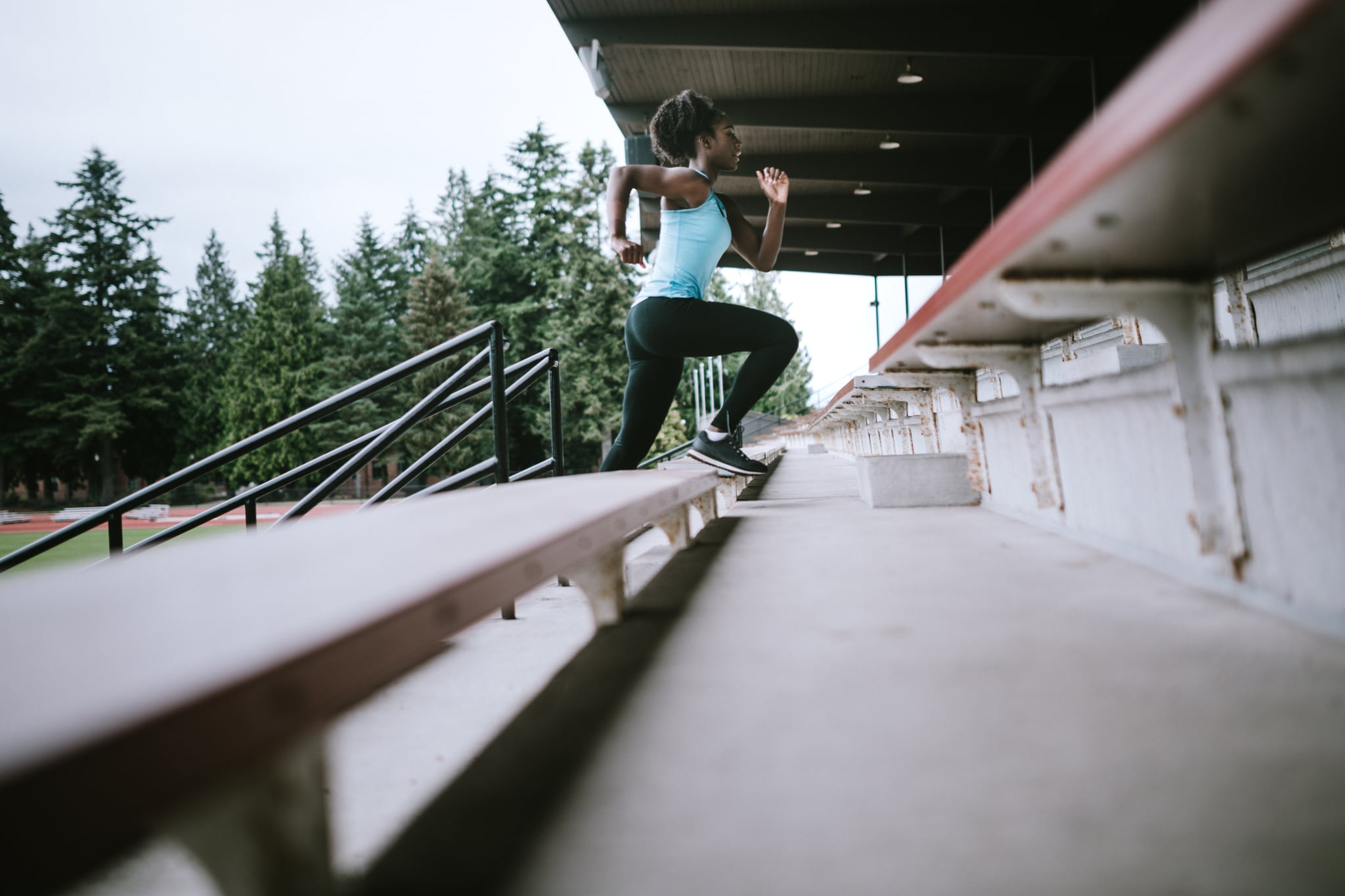 A young woman does sprints up and down the stadium stairs to build speed and strength, training for her next track meet. Horizontal image with copy space.