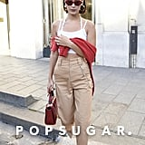 Bella Wore a White Crop Top, Beige High-Waist Trousers, and a Red Sweater Hanging Around Her Shoulders