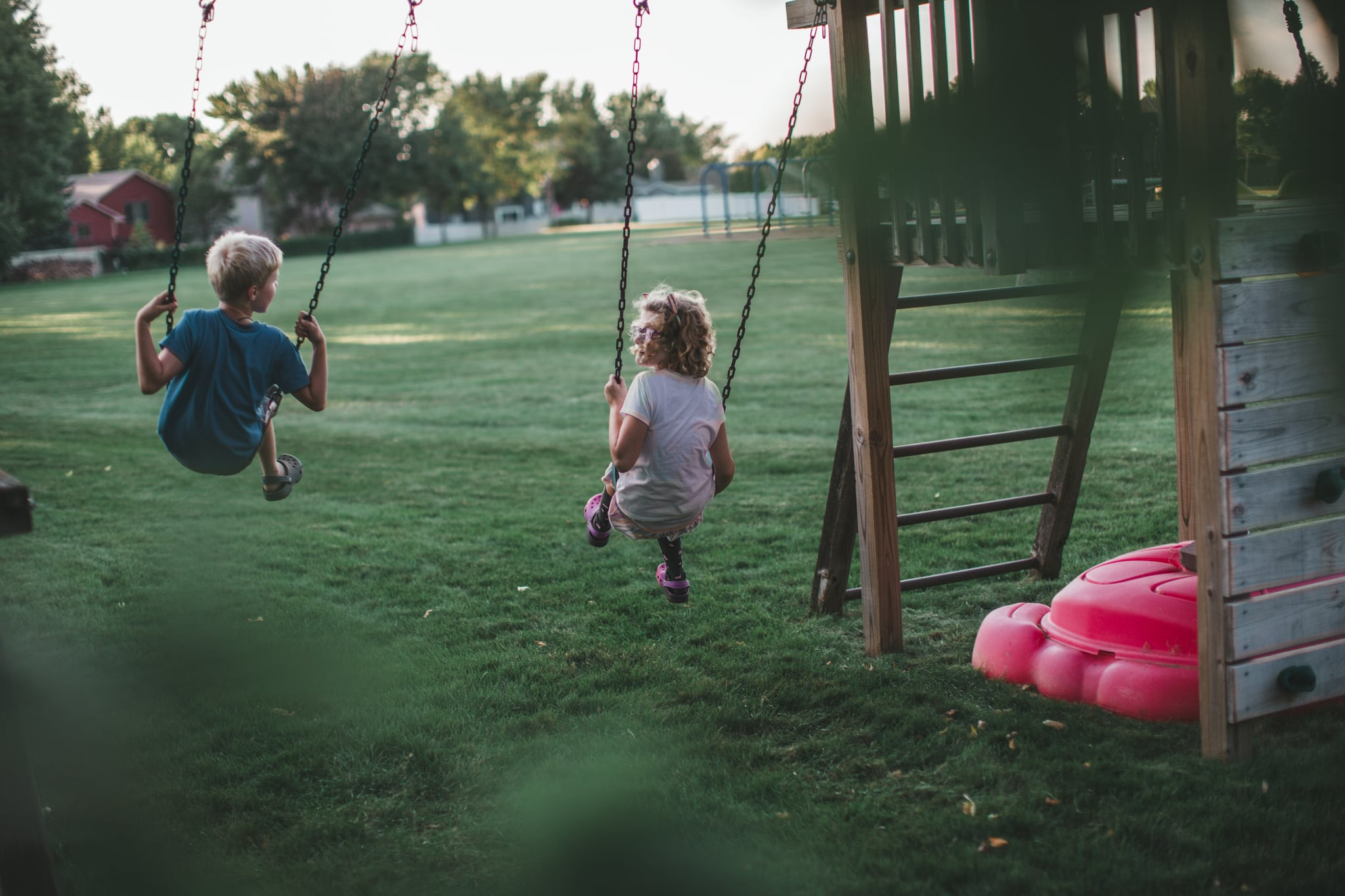 Girl and boy play together on a backyard swing set playground swinging back and forth while looking at each other and chatting.