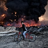October 21: A boy passes an oil field that was set on fire by retreating ISIS fighters in Qayyarah, Iraq.