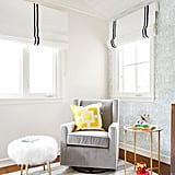 A glider and mohair stool make this cozy corner perfect for nursing, giving a bottle, or just getting in some good cuddle time. The roman shades are lined with blackout fabric, a must have for napping babies.