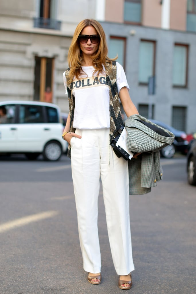 Mixing and matching in understated trousers, a t-shirt, and a sequined vest.