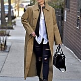 Karlie Kloss artfully mastered the layering look in NYC with a button down, zip-up sweater, and trench coat.