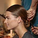 Lead stylist Paul Hanlon designed an equestrian-inspired hairstyle, leaving not a single hair out of place. To create the sleek low bow in back, he applied a generous portion of Fekkai Full Blown Styling Whip to damp hair before blow-drying it straight. After dividing hair into sections, he applied hair spray to each section, again blow-drying it back toward the nape of the neck. Next, he gathered the hair into a tight ponytail and looped it around the base of the ponytail. A spray of Fekkai Brilliant Glossing Sheer Shine Mist added even more shine.