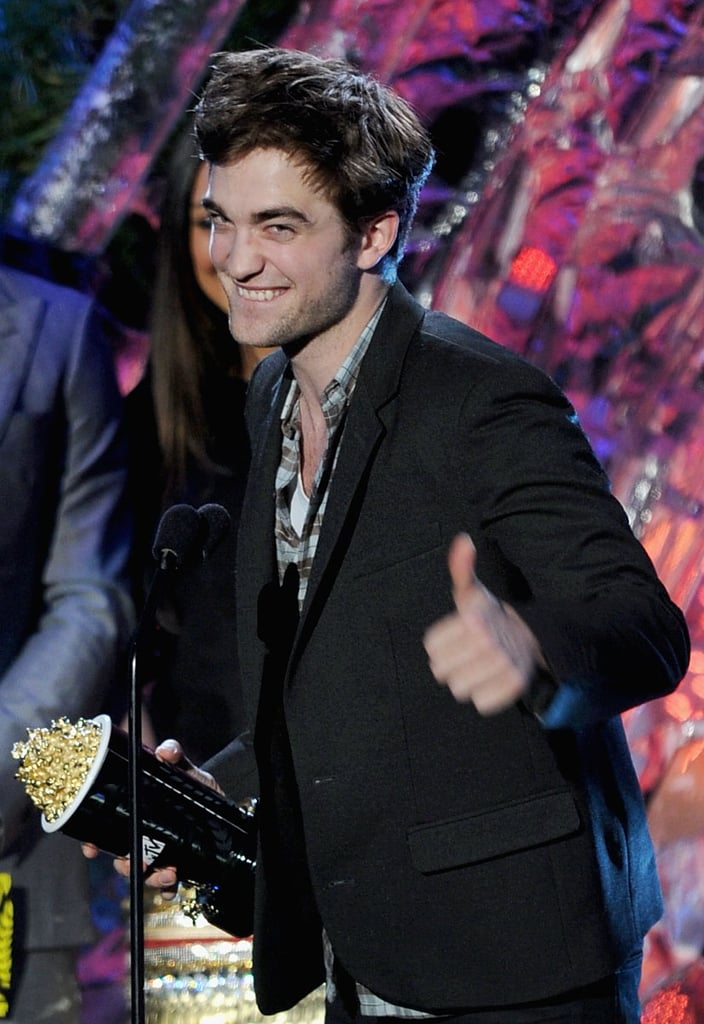 Robert Pattinson bit his lip and gave an adorable thumbs-up as he accepted the golden popcorn for best male performance at the MTV Movie Awards in Universal City this evening. He accepted the first honor of the night, which bodes well for all the categories Eclipse is nominated in. Robert bypassed posing for cameras on the way in, but Kristen Stewart rocked a tiny Balmain dress to hit the red carpet. The two are sitting side by side in the audience, and were spotted laughing together before Robert won. Friends With Benefits leading duo Justin Timberlake and Mila Kunis presented the award to Rob, and JT got a little handsy with his sexy costar. Robert and Kristen could have their own intimate moment on stage if they make it a three-peat in the best kiss category. In the past they've teased fans with almost lip-locks, though according to Robert they have nothing planned this time around. They'll also help present the first Breaking Dawn trailer, which made its debut online earlier today.