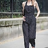 A polka-dot jumpsuit, sandals, and sleek earrings are perfect in Summer.