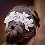 This nylon comb ($78) features three sparkly sequin-and-rhinestone flowers with silver beaded leaves. Wear it over a hair bun to give your entire look more oomph.