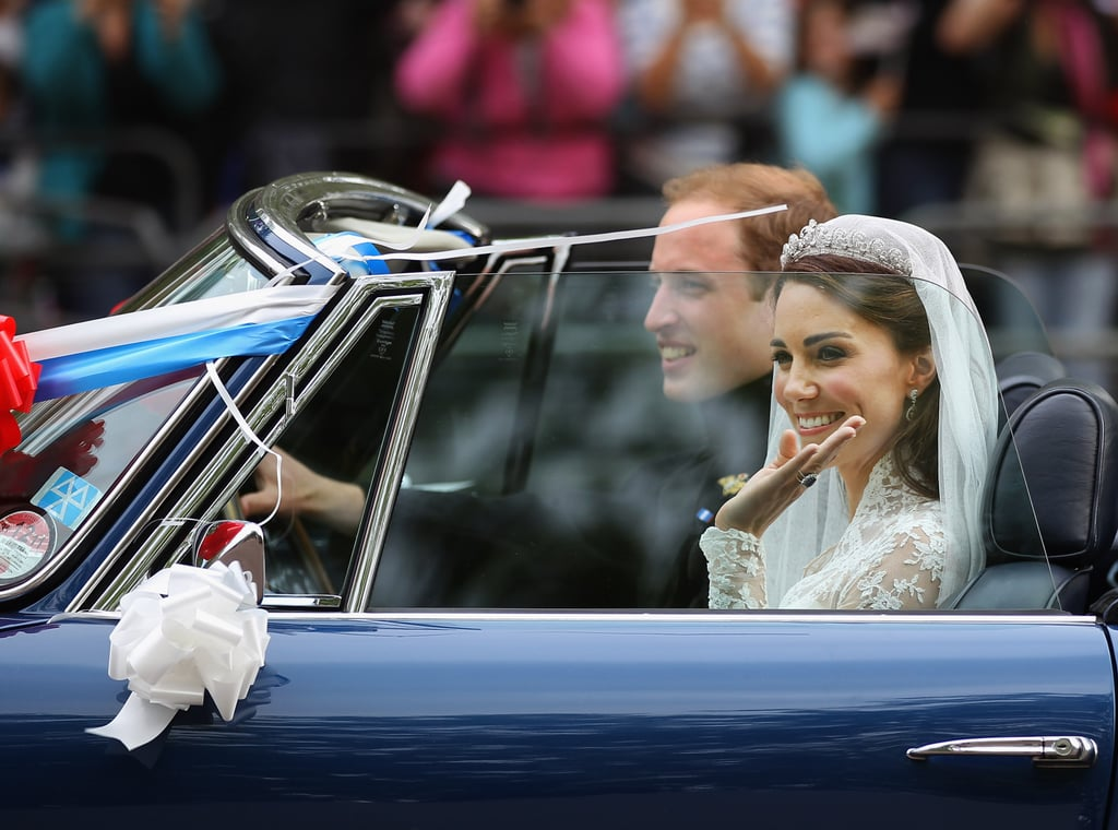 """Kate Middleton and Prince William beamed as they left the royal wedding brunch reception in an Aston Martin. Will was behind the wheel of the car, which was decorated with balloons, a big red ribbon, and a license plate that read """"JU5T WED."""" Kate, still wearing her Alexander McQueen wedding gown, waved to the gathered crowds as they rolled by. The newlyweds' decision to drive themselves was a modern one, as was the car, which Prince Charles had converted to run on eco-friendly, bio-ethanol fuel! The pair's festivities aren't yet over, though. They'll be on hand this evening for a private party hosted by William's father."""