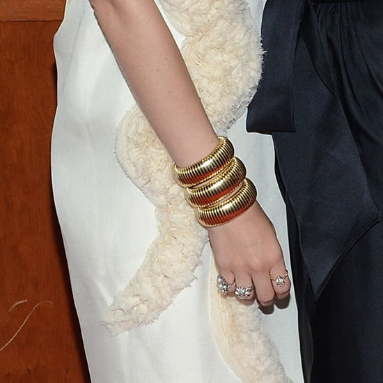On her right hand, Ashley paired a gold coiled bracelet with multiple shiny rings. To achieve her look, wear this Michael Kors snake wrap bracelet ($131, originally $175) with this Judith Jack pearl ring ($198), this Forever 21 bejeweled flower ring ($4), and this Soixante Neuf teardrop ring ($92).