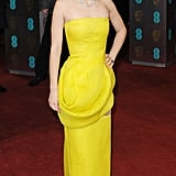 Marion Cotillard battled the gray skies in a vibrant yellow Christian Dior Haute Couture gown at the BAFTA Awards in London. The actress accessorized with a swept updo, red lipstick, and a dazzling diamond necklace by Chopard.