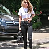 Wearing black jeans from the Joan Smalls x True Religion collaboration with a knotted white t-shirt and white sneakers.