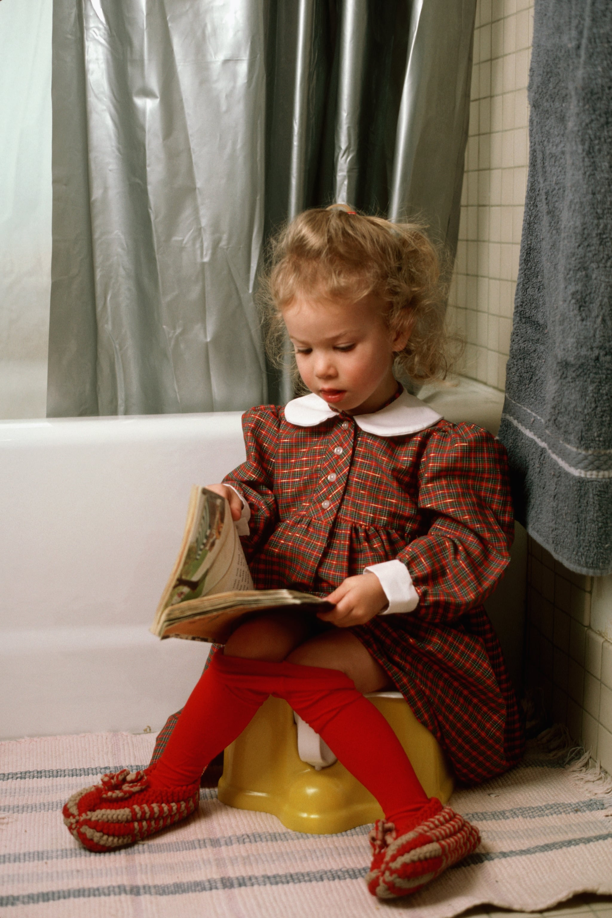 2 year-old girl sitting on training potty seat. (Photo by James Marshall/Corbis via Getty Images)