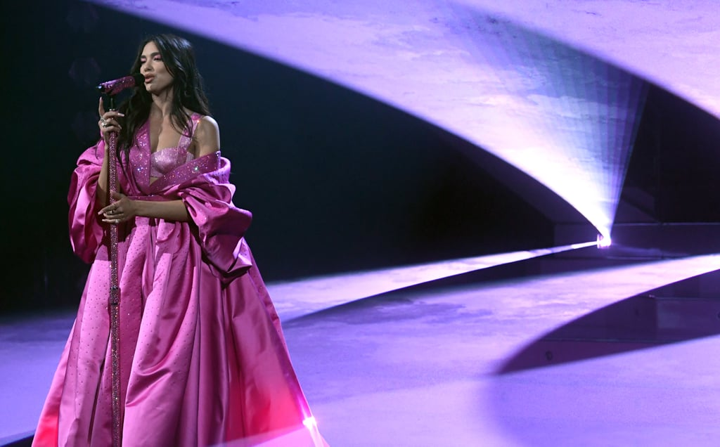 """Dua Lipa pulled out all the stops for her performance at the 2021 Grammys, stunning in not one, two, but three head-to-toe custom pink outfits, courtesy of Versace. She first stepped onstage Sunday evening in a glittery magenta gown draped over a matching sequin bra top to perform """"Levitating"""" with DaBaby, and that look alone was a winner. With eye makeup, nails, and even her mic matching the Barbie pink shade, she certainly committed to the concept. Then, mid-performance, she swapped the robe-like dress for a lilac oversize blazer with — you guessed it — flashy magenta boots to match. And for the grand finale, as she transitioned into her solo """"Don't Start Now"""" performance, she casually threw off the blazer to reveal her sexy sequin two-piece set. The singer, who was nominated for six Grammys this year, kept the pink theme going all night, starting off the evening in an ethereal Versace butterfly gown that truly sparkled from every angle. Ahead, check out Dua looking like the pop queen she is in her gorgeous Grammys performance looks.      Related:                                                                                                           The Stylish, Star-Packed Grammys Red Carpet Was Music to Our Ears"""