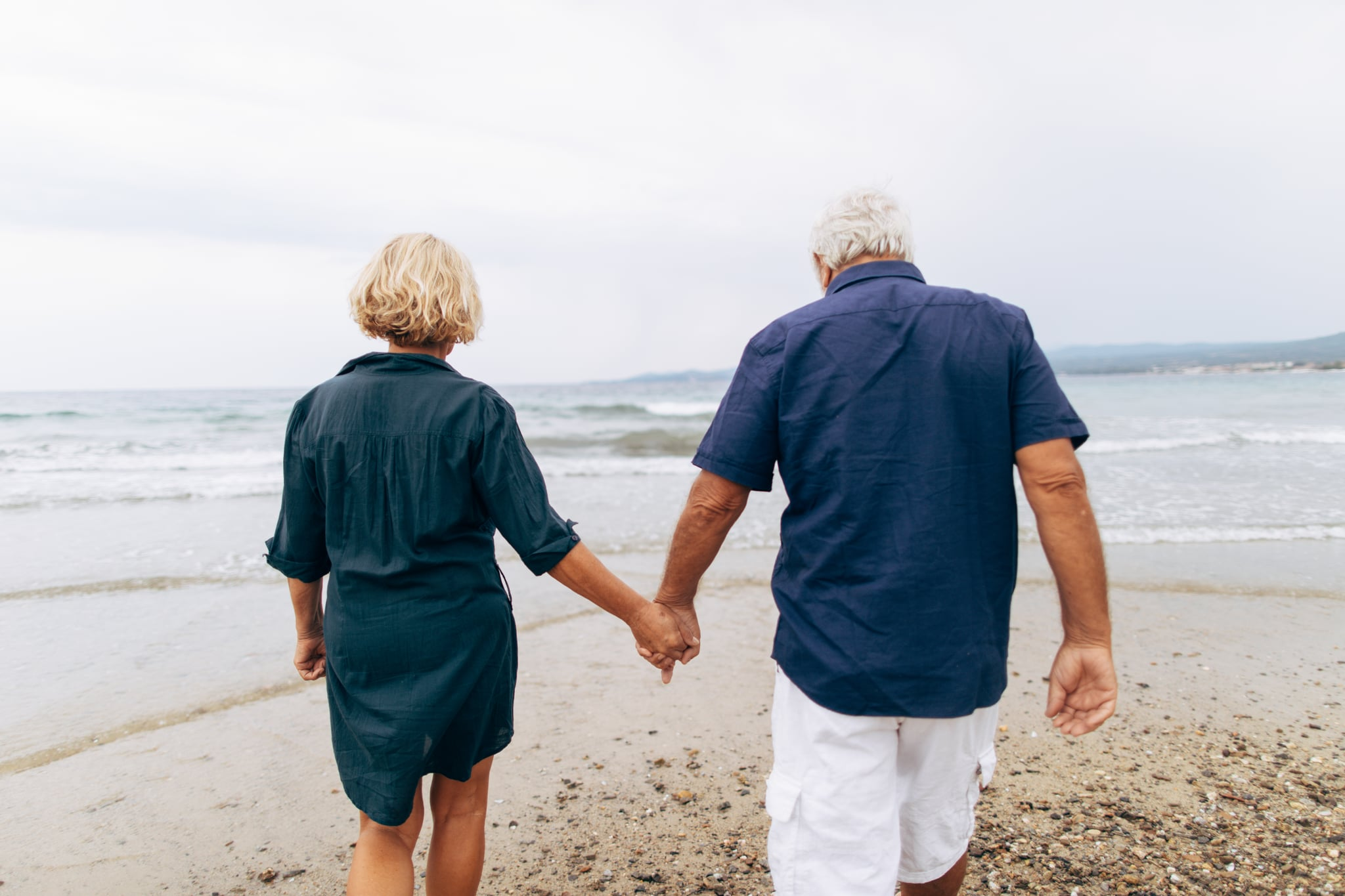 Photo of senior couple having a romantic walk by the sea while holding hands