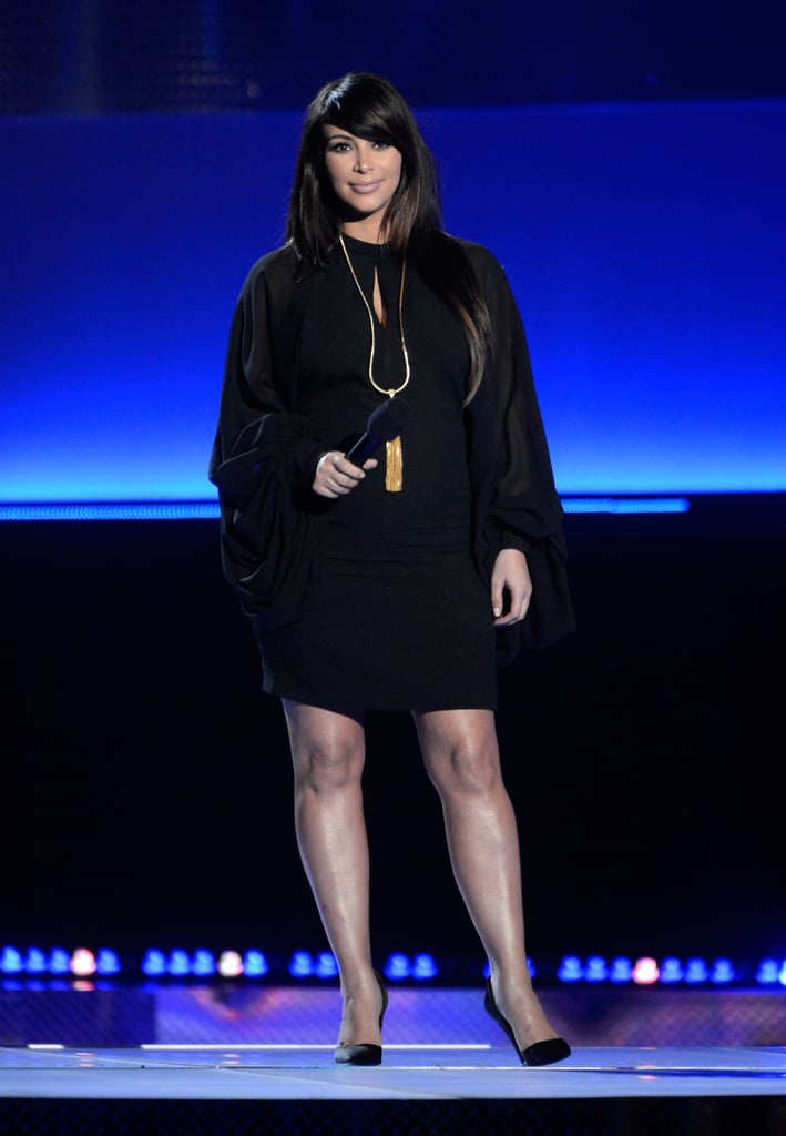"Kim Kardashian put a protective hand over her baby bump this evening on the MTV Movie Awards red carpet in LA. The mom-to-be wore a little black dress with draped sleeves for her entrance and her time on stage. She took the microphone to present Selena Gomez's performance of ""Come and Get It."" Kim is home in LA following a weekend getaway. She went to Las Vegas for a signing at her Kardashian Khaos store on behalf of her new fragrance, Glam. Tonight, though, she's taking on duties as a presenter at the show, along with other celebs like Brad Pitt and Melissa McCarthy. What do you make of Kim's look? Make sure to vote in all of our MTV Movie Awards fashion and beauty polls."