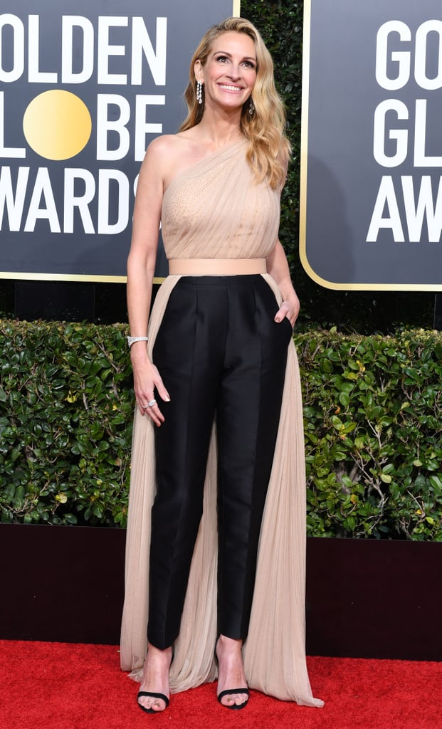 Julia Roberts really brought her A-game to the 2019 Golden Globes on Sunday in an unforgettably chic pantsuit. Dressed to the nines, the Homecoming actress opted for a Stella McCartney number with tailored black trousers and a flowing champagne tulle top. If you caught her shining on the red carpet, it's probably thanks to the delicate rhinestone detailing underneath.  It's no surprise Julia opted for a sophisticated pantsuit; they've been an essential part of her style evolution since the '90s. She paired her elegant look with Chopard jewellery and strappy black heels. Ahead, see Julia's glam outfit from all angles.       Related:                                                                                                           Julia Roberts Has a Street Style Secret Weapon, and It's a Pair of Leather Pants