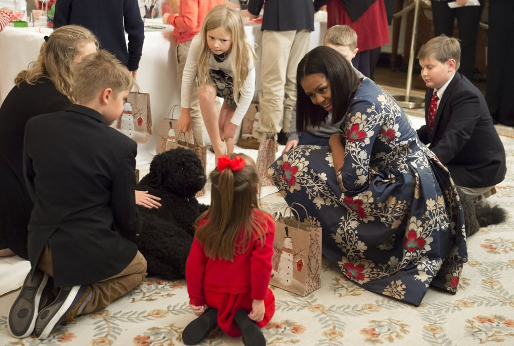 In late November Michelle brought the first dogs, Sunny and Bo, to bond with a group of military families at the White House, where they admired Christmas decorations.