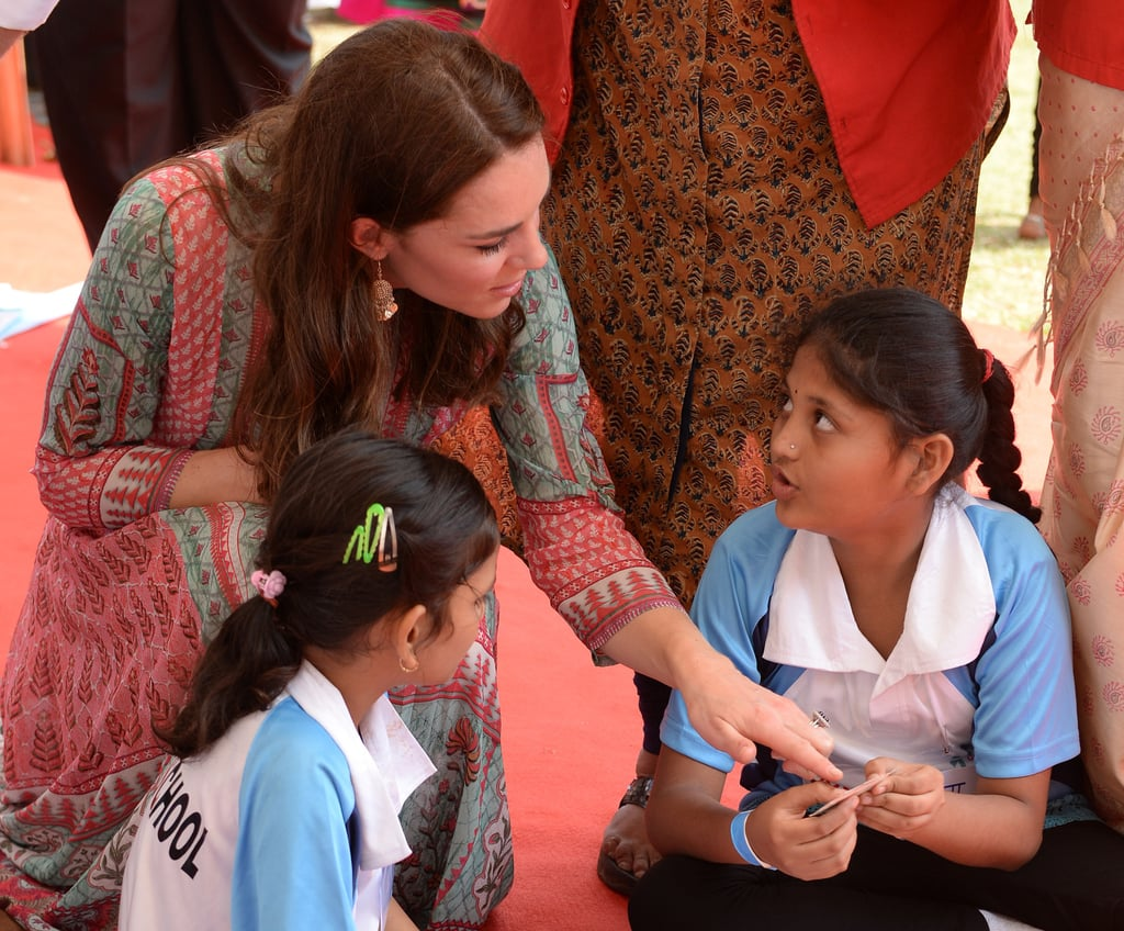 While visiting India in April 2016, Kate knelt down to speak to a group of students after a cricket match.