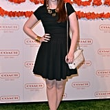 Michelle Trachtenberg's black fit-and-flare dress played the dark counterpart to her lighter accessory fare. The actress toted a quilted Poppy chain bag by Coach and wore reptilian-print pumps and a costume statement necklace.
