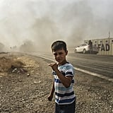 A boy watches as Turkish forces drive toward the Syrian border.
