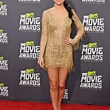 Selena showed up to the MTV Movie Awards red carpet looking absolutely stunning in a gold long-sleeved fringe minidress from Julien Macdonald's Fall 2013 collection. She kept her focus on the flirty frock with a pair of Jimmy Choo platforms, and gave the look an edgy spin with a slick braided ponytail.