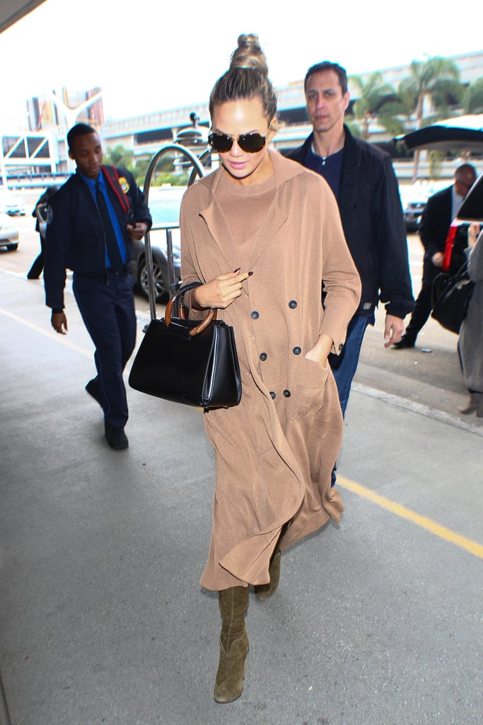 Chrissy covered up in a neutral buttoned coat for a flight, carrying her black leather satchel and wearing oversize sunglasses.